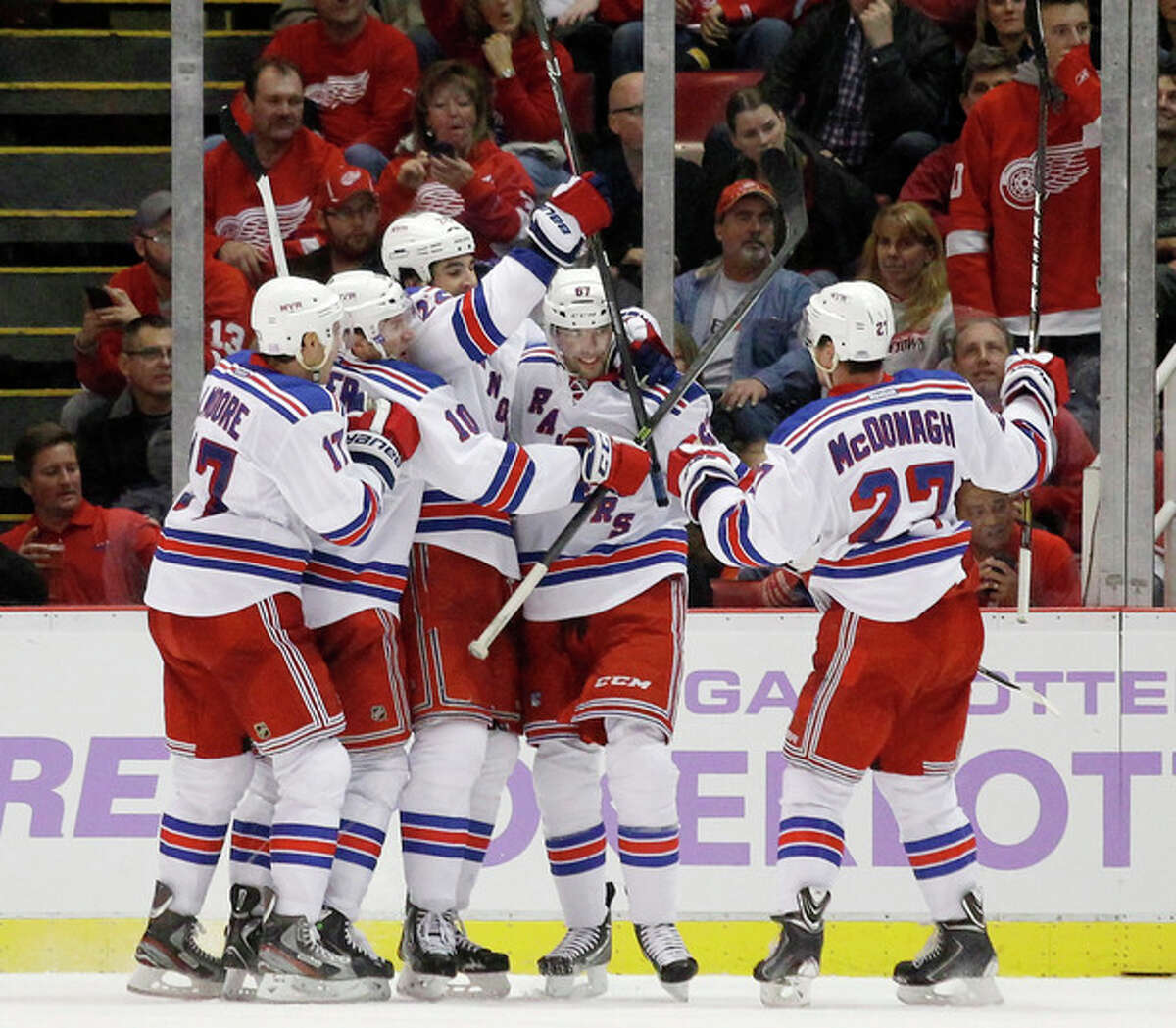 New York Rangers left wing Benoit Pouliot, second from right, celebrates his second period goal against the Detroit Red Wings with teammates John Moore (17), J.T. Miller (10), Brian Boyle (22) and Ryan McDonagh (27) during an NHL hockey game Saturday, Oct. 26, 2013, in Detroit. (AP Photo/Duane Burleson)