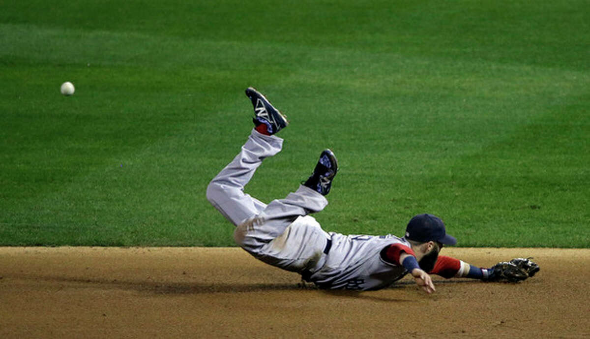 Boston Red Sox's Dustin Pedroia dives for a ball hit by St. Louis Cardinals' Kolten Wong during the eighth inning of Game 3 of baseball's World Series Saturday, Oct. 26, 2013, in St. Louis. (AP Photo/Charlie Neibergall)