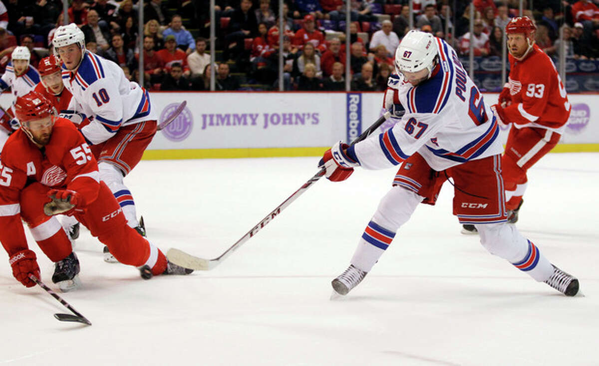 New York Rangers left wing Benoit Pouliot (67) takes a shot against Detroit Red Wings defenseman Niklas Kronwall (55), of Sweden, during the first period of an NHL hockey game Saturday, Oct. 26, 2013, in Detroit. (AP Photo/Duane Burleson)