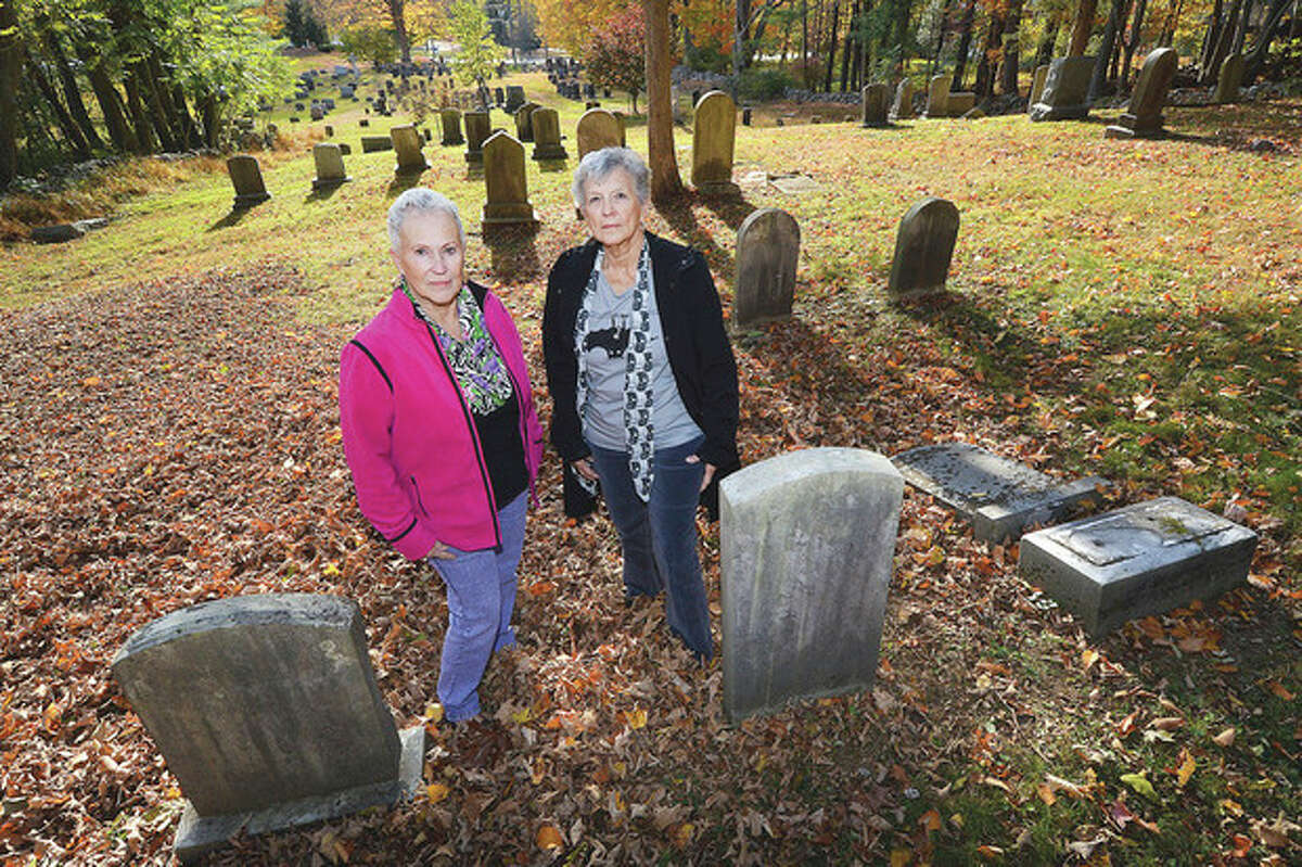 Hour photo / Alex von Kleydorff At St. Matthews Cemetery, sisters Jeanne Brown, left, and Betsy Kondub stand next to the graves of their great grandmother and great grandfather Annie Betts Jones and James Jones. The stone at right that is tipped over marks the grave of Jones' first wife, Fannie Durand.