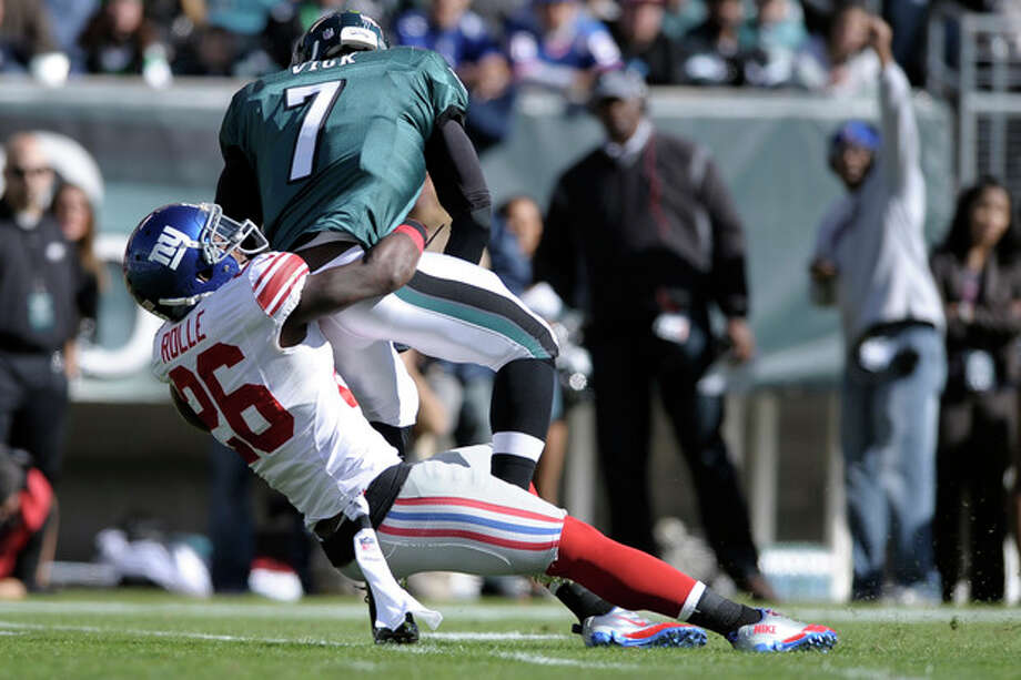 New York Giants strong safety Antrel Rolle (26) sacks Philadelphia Eagles quarterback Michael Vick (7) during the first half of an NFL football game on Sunday, Oct. 27, 2013, in Philadelphia. (AP Photo/Michael Perez) / FR168006 AP
