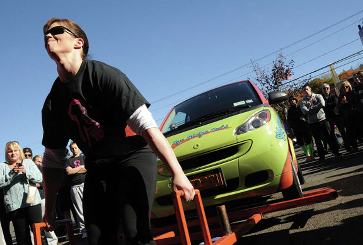 April Ciaffagione lifts a compact car Sunday at the Battle of the Belles strongwoman competition held at Punch Kettelbell Gym in Norwalk. Hour photo/Matthew Vinci