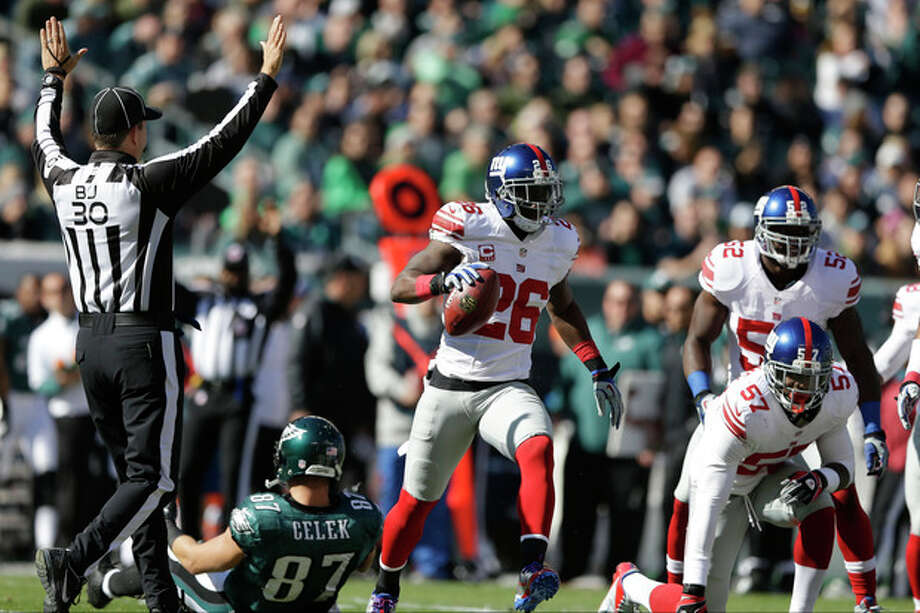 New York Giants strong safety Antrel Rolle (26) celebrates while running away from Philadelphia Eagles tight end Brent Celek (87) after intercepting a pass during the first half of an NFL football game on Sunday, Oct. 27, 2013, in Philadelphia. (AP Photo/Matt Rourke) / AP