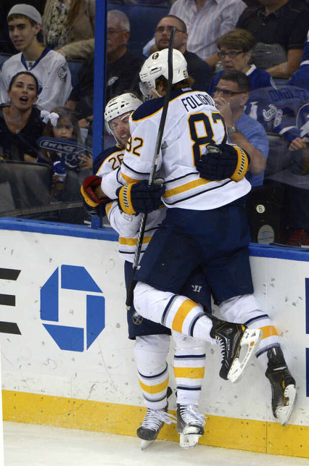 Buffalo Sabres left wing Thomas Vanek (26) is congratulated by left wing Marcus Foligno (82) after Vanek scored a goal during the third period of an NHL hockey game against the Tampa Bay Lightning in Tampa, Fla., Saturday, Oct. 26, 2013.(AP Photo/Phelan M. Ebenhack)