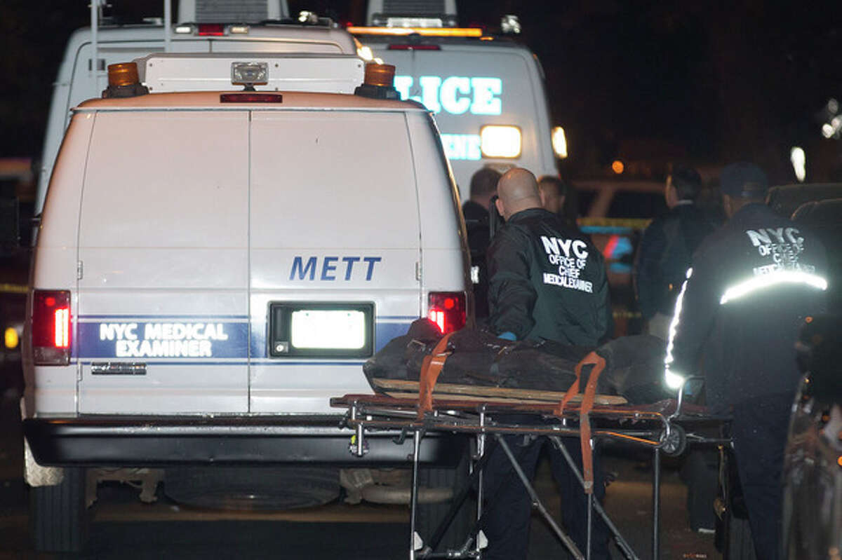 Medical Examiner Transport personnel prepare to place a loaded body bag into their vehicle after exiting the residence of a crime scene in the Sunset Park neighborhood of Brooklyn Sunday, Oct. 27, 2013 where five people, including a toddler, were stabbed to death earlier in New York. Emergency responders found three of the victims dead at the residence just before 11 p.m. Saturday. Two others were taken to Brooklyn hospitals, where they were pronounced dead. (AP Photo/John Minchillo)