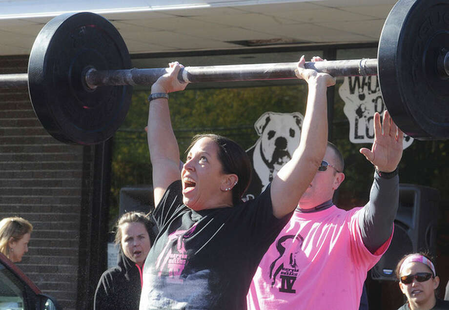 Judy DeCambra competes in the press medley event Sunday at the Battle of the Belles strongwoman competition held at Punch Kettlebell Gym in Norwalk.