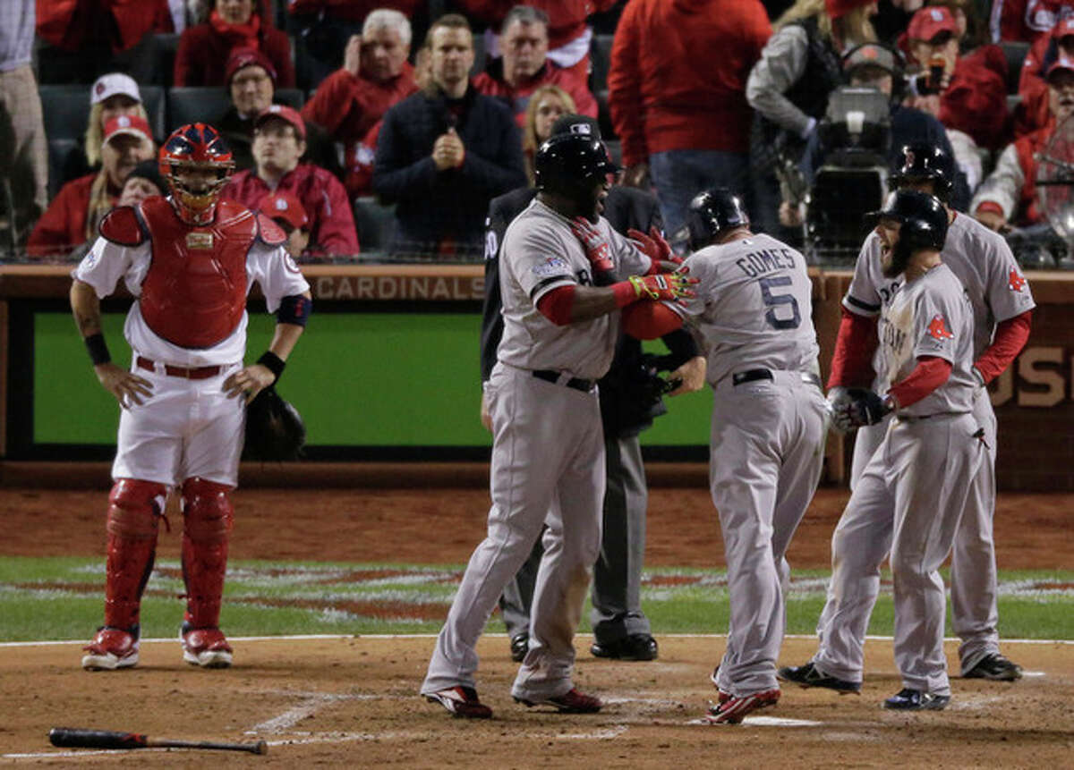 Boston Red Sox's Jonny Gomes (5) celebrates at home after hitting a three-run home run during the sixth inning of Game 4 of baseball's World Series against the St. Louis Cardinals Sunday, Oct. 27, 2013, in St. Louis. (AP Photo/Charlie Riedel)