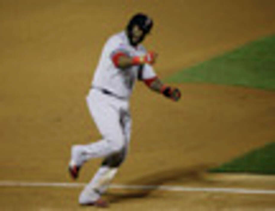 Boston Red Sox David Ortiz celebrates Jonny Gomes' three run home run off of St. Louis Cardinals relief pitcher Seth Maness as he scores during the sixth inning of Game 4 of baseball's World Series Sunday, Oct. 27, 2013, in St. Louis. Ortiz scored off of Gomes' home run. (AP Photo/Charlie Neibergall) / AP