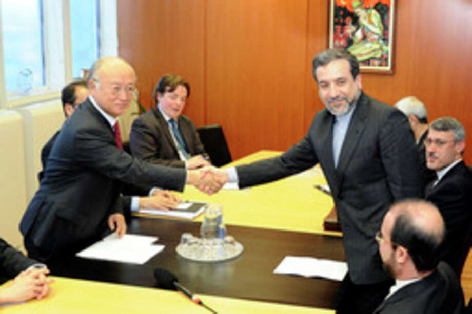 Iran's deputy Foreign Minister Abbas Araghchi, right, and Director General of the International Atomic Energy Agency, IAEA, Yukiya Amano shake hands prior to a meeting at the International Center in Vienna, Austria on Monday, Oct. 28, 2013. The meeting was held before agency experts meet Iranian diplomats in a renewed push to probe suspicions that Tehran worked on nuclear arms. (AP Photo/Hans Punz) / AP