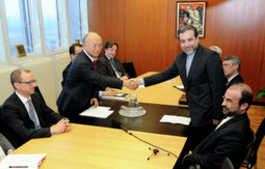 Iran's deputy Foreign Minister Abbas Araghchi, right, and Director General of the International Atomic Energy Agency, IAEA, Yukiya Amano shake hands next to IAEA deputy director general Tero Tapio Varjoranta, left, and Iran's Ambassador to the International Atomic Energy Agency, IAEA, Reza Najafi, right, prior a meeting at the International Center in Vienna, Austria on Monday, Oct. 28, 2013. The meeting was held before agency experts meet Iranian diplomats in a renewed push to probe suspicions that Tehran worked on nuclear arms. (AP Photo/Hans Punz) / AP