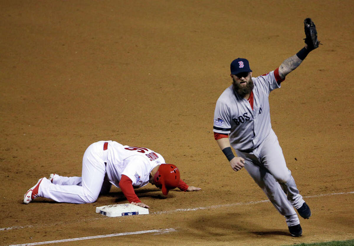 Boston Red Sox first baseman Mike Napoli celebrates after tagging out St. Louis Cardinals' Kolten Wong on a pick-off attempt to end Game 4 of baseball's World Series Sunday, Oct. 27, 2013, in St. Louis. The Red Sox won 4-2 to ties the series at 2-2. (AP Photo/David J. Phillip)