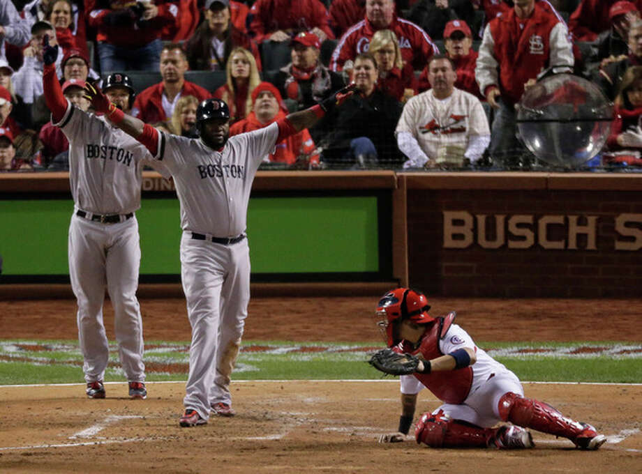 Boston Red Sox's David Ortiz reacts after sliding safely past St. Louis Cardinals catcher Yadier Molina during the fifth inning of Game 4 of baseball's World Series Sunday, Oct. 27, 2013, in St. Louis. Ortiz scored from third on a sacrifice fly by Stephen Drew. (AP Photo/Charlie Riedel) / AP