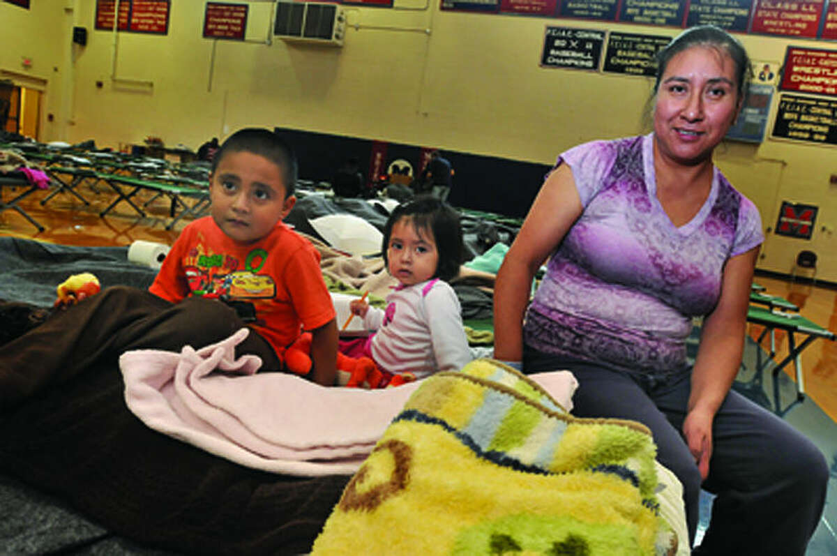 Maria DeJesus and her children, Diego 4 and Casey 2, are set up for the overnight stay at Brien McMahon high school Monday. The Red Cross has the gym available as a shelter from hurrican Sandy. hour photo/Matthew Vinci
