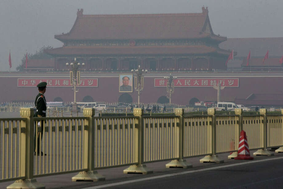 Paramilitary policemen guard and patrol on Tiananmen Square, near Tiananmen Gate, back, where state media says a sports-utility vehicle veered into a crowd, in Beijing, China, Monday, Oct. 28, 2013. The vehicle crashed and caught fire Monday, killing three occupants and injuring tourists and security officers, police said. Several people in the crowd were injured in the crash in front of the iconic Tiananmen Gate around noon, a statement posted on the Beijing police's microblog said. (AP Photo/Alexander F. Yuan) / AP