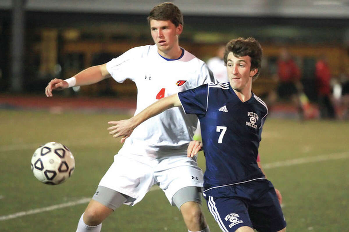 Hour Photo/Chris Palermo Wilton's Brendan Devane goes up against a Greenwich defender during the FCIAC semifinals Monday night at Fairfield Ludlow High School.