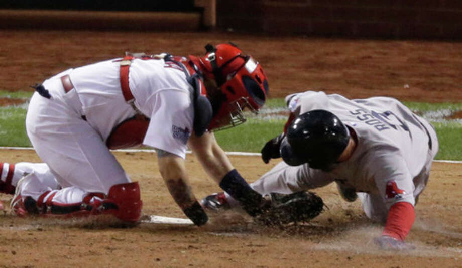 Boston Red Sox's David Ross is tagged out at home by St. Louis Cardinals catcher Yadier Molina during the seventh inning of Game 5 of baseball's World Series Monday, Oct. 28, 2013, in St. Louis. (AP Photo/Charlie Riedel) / AP