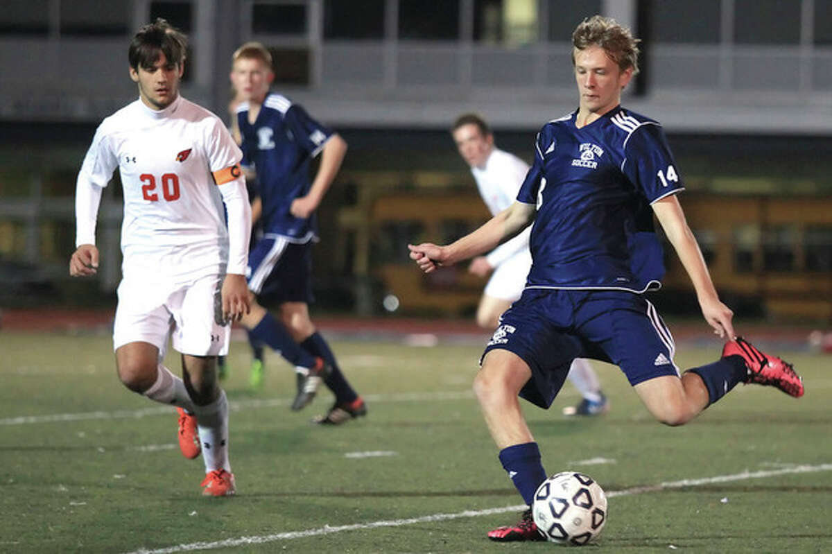 Hour Photo / Chris Palermo. Wilton's Oliver Quantock kicks the ball upfield past a Greenwich defender during the FCIAC semifinals Monday night at Fairfield Ludlow High School.
