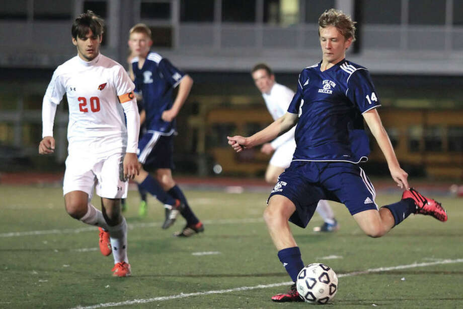 Hour Photo / Chris Palermo. Wilton's Oliver Quantock kicks the ball upfield past a Greenwich defender during the FCIAC semifinals Monday night at Fairfield Ludlow High School. / © 2013 Hour Newspapers All Rights Reserved