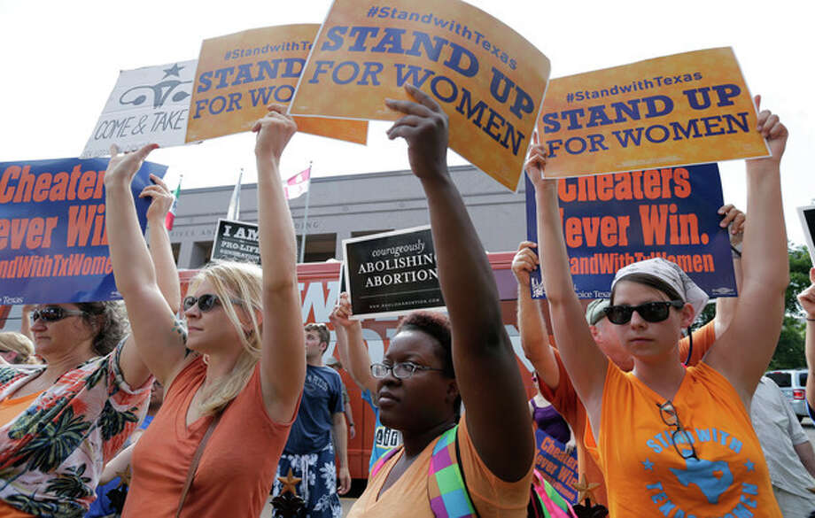 File - In this July 9, 2013 file photo, opponents and supporters of an abortion bill hold signs near a news conference outside the Texas Capitol, in Austin, Texas. New abortion restrictions passed by the Texas Legislature are unconstitutional and will not take effect as scheduled on Tuesday, a federal judge has ruled. (AP Photo/Eric Gay, File) / AP