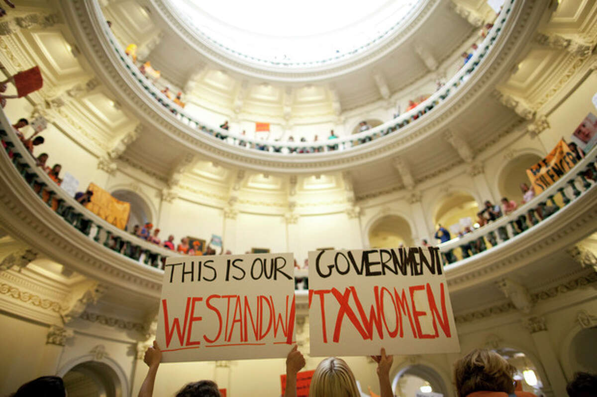 FILE - In this July 12, 2013 file photo, abortion rights supporters rally on the floor of the State Capitol rotunda in Austin, Texas. New abortion restrictions passed by the Texas Legislature are unconstitutional and will not take effect as scheduled on Tuesday, Oct. 29, 2013, a federal judge has ruled. (AP Photo/Tamir Kalifa, File)