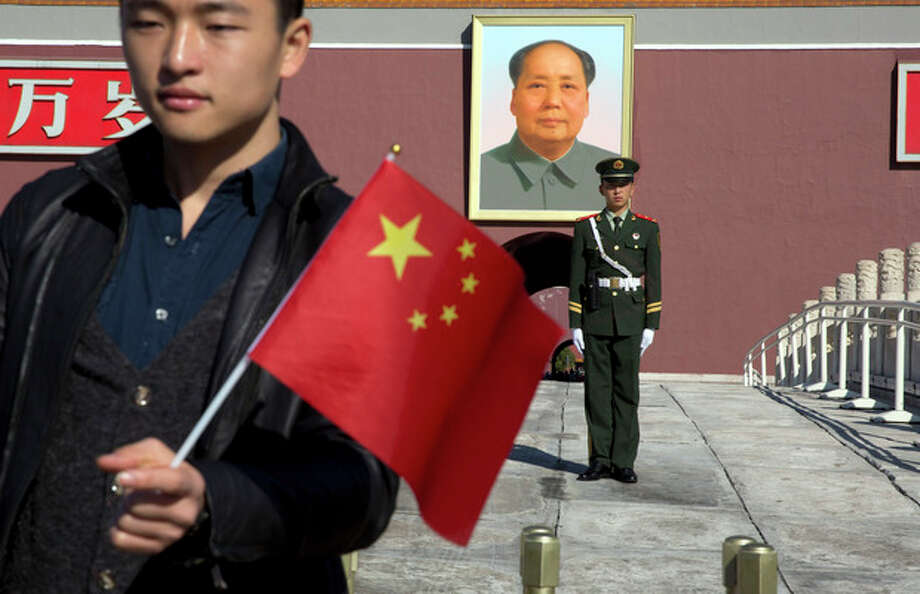 A tourist holds up a Chinese flag as he poses for photos near a Chinese paramilitary policeman on duty in front of former Chinese leader Mao Zedong's portrait on Tiananmen Gate, close to the site of an incident Monday where a car plowed through a crowd before it crashed and burned in Beijing, China, Tuesday, Oct. 29, 2013. Police investigating the apparent car attack at Beijing's Forbidden City searched Tuesday for information on two ethnic Uighur minority suspects, a hotel employee said, a day after the incident which killed five people and injured 38.(AP Photo/Ng Han Guan) / AP