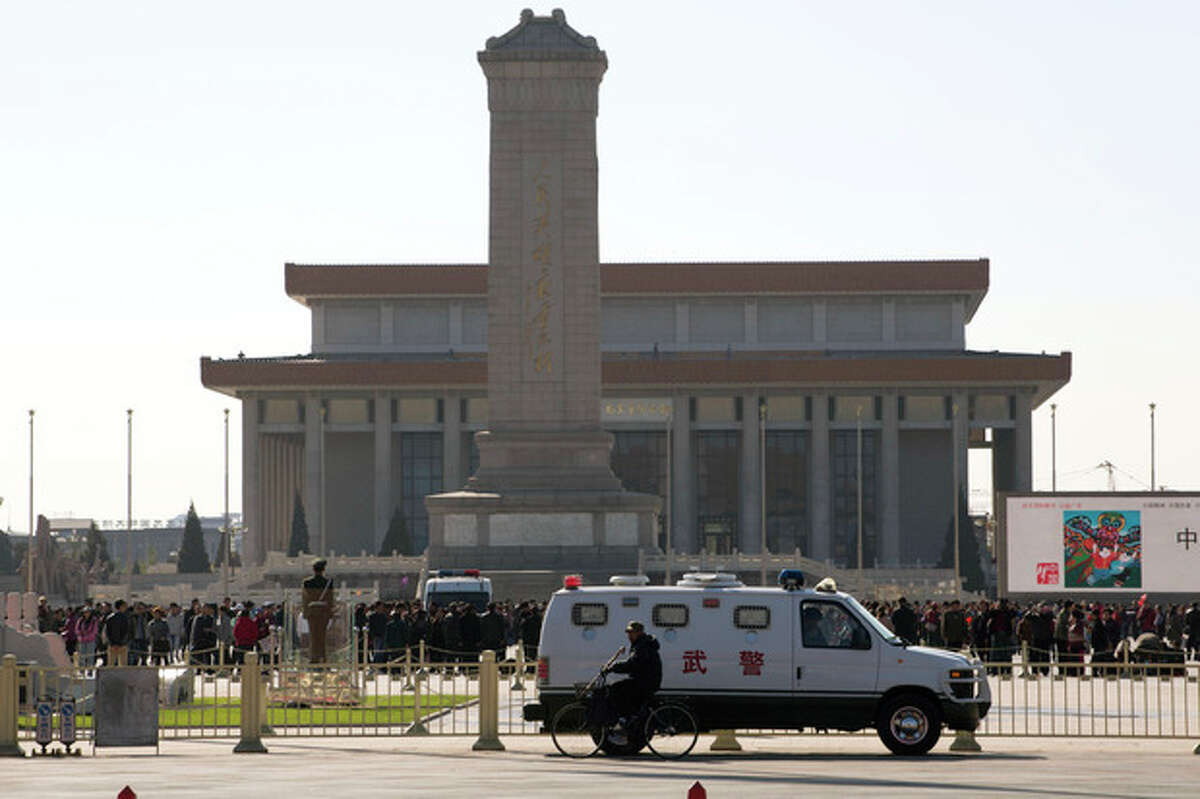 An armored Chinese paramilitary vehicle is stationed near Tiananmen Square across the street from Tiananmen Gate, the site of an incident Monday where a car plowed through a crowd before it crashed and burned in Beijing, China, Tuesday, Oct. 29, 2013. Police investigating the apparent car attack at Beijing's Forbidden City searched Tuesday for information on two ethnic Uighur minority suspects, a hotel employee said, a day after the incident which killed five people and injured 38. (AP Photo/Ng Han Guan)