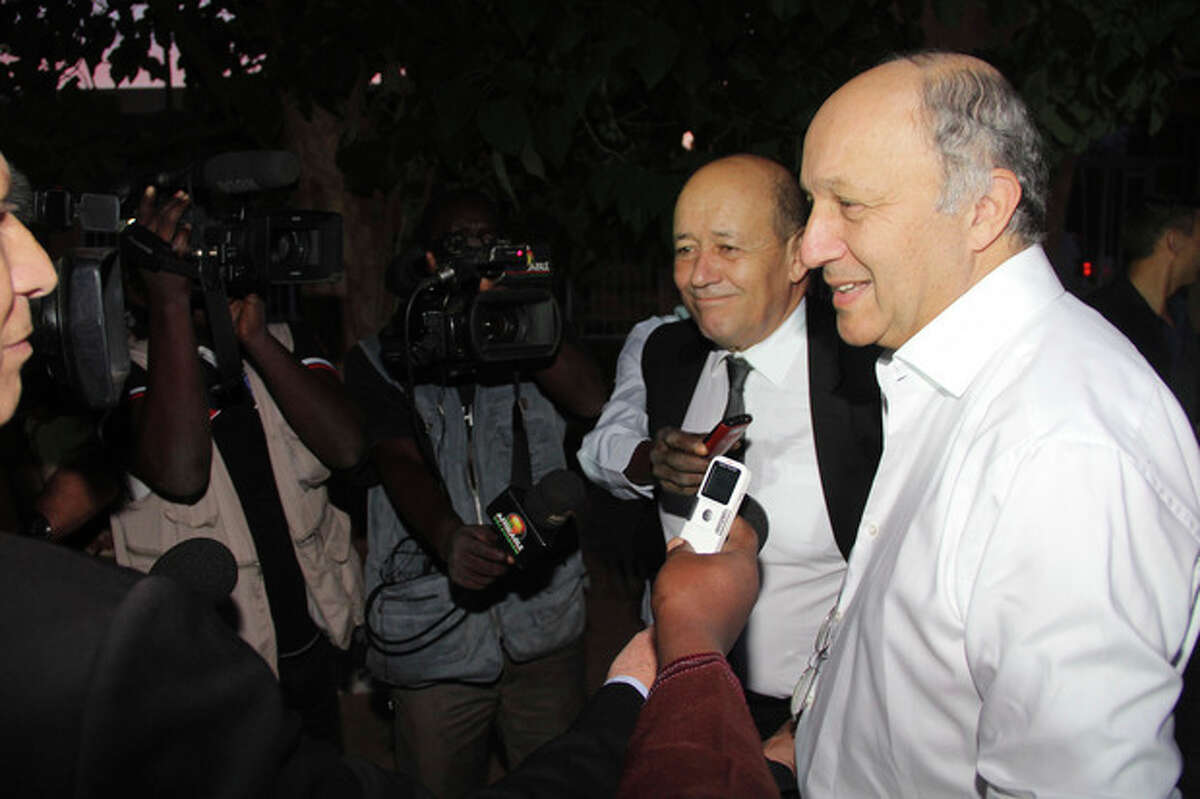 French Foreign Minister Laurent Fabius, right, answers questions from the press as he accompanies four freed French hostages on their departure from the airport in Niamey, Niger, Wednesday, Oct. 30, 2013. Four Frenchmen held hostage by al-Qaida militants for three years in the African Sahel headed home to France Wednesday, one day after their release. France's President Francois Hollande and their families will meet the men at a military airport outside Paris later Wednesday in what is expected to be an emotional homecoming. (AP Photo/Tagaza Djibo)
