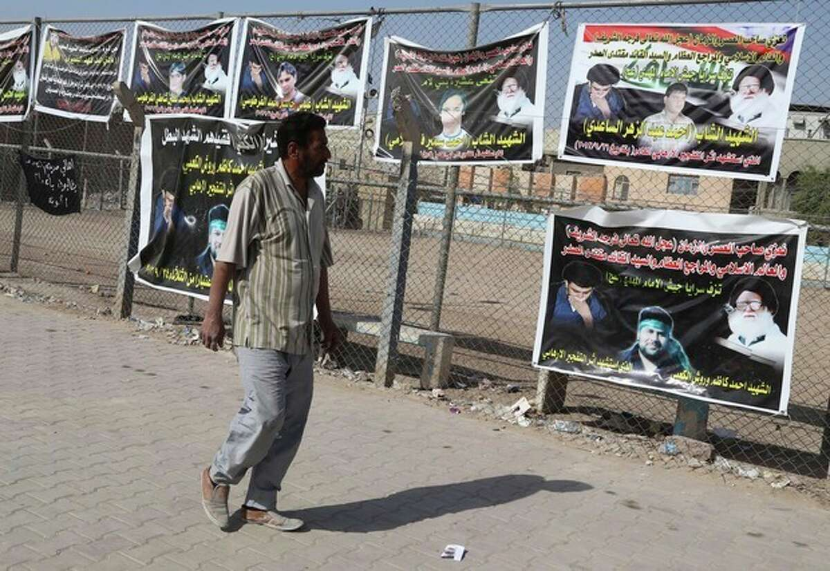 In this photo taken Friday, Oct. 25, 2013, a man walks past posters of Shiite people who were killed during recent attacks in Sadr city in Baghdad, Iraq. The wave of attacks by al-Qaida and Sunni extremists that has killed thousands of Iraqis in 2013 so far, most of them Shiites, is provoking ominous calls from Shiite leaders to take up arms in self-defense. Iraq?'s Shiite prime minister, Nouri al-Maliki, who will meet with U.S. President Barack Obama on Friday, Nov. 1, 2013, said he wants American help in quelling the violence. (AP Photo/Karim Kadim)