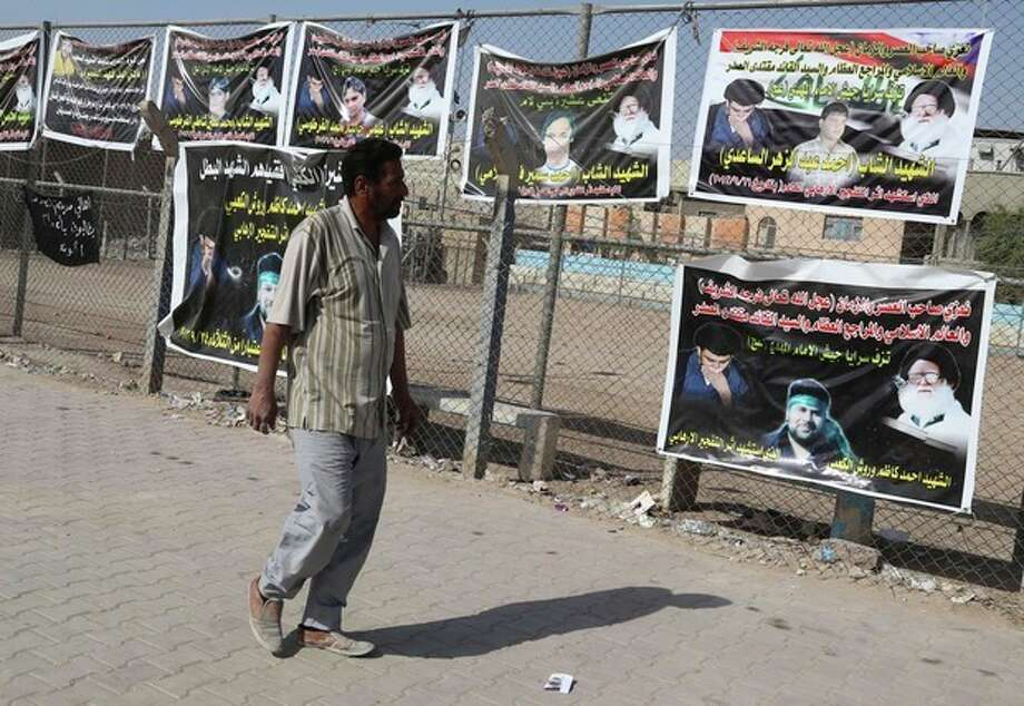 In this photo taken Friday, Oct. 25, 2013, a man walks past posters of Shiite people who were killed during recent attacks in Sadr city in Baghdad, Iraq. The wave of attacks by al-Qaida and Sunni extremists that has killed thousands of Iraqis in 2013 so far, most of them Shiites, is provoking ominous calls from Shiite leaders to take up arms in self-defense. Iraq's Shiite prime minister, Nouri al-Maliki, who will meet with U.S. President Barack Obama on Friday, Nov. 1, 2013, said he wants American help in quelling the violence. (AP Photo/Karim Kadim) / AP