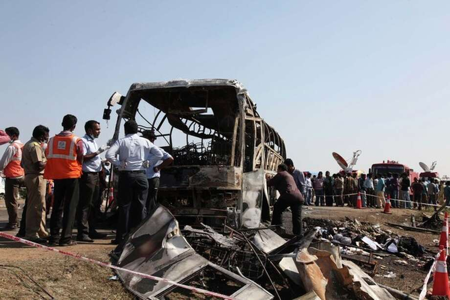 Officials inspect the scene after a bus crashed into a highway barrier and erupted in flames at Mehabubnagar in southern Andhra Pradesh state, India, Wednesday, Oct. 30, 2013. According to officials many of the passengers were burned alive in the accident that happened early Wednesday. (AP Photo/Mahesh Kumar A.) / AP