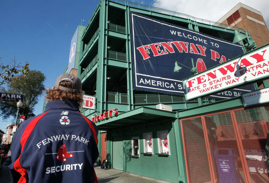 A security guard keeps an eye on things outside Gate D at Fenway Park in Boston, Tuesday, Oct. 29, 2013. If the Boston Red Sox are able to win the baseball World Series at at the stadium, police and city officials want to make sure fans celebrate responsibly. Boston holds a 3-2 lead over the St. Louis Cardinals with Game 6 and if necessary Game 7 scheduled at Fenway for Wednesday and Thursday nights. Police plan to put extra patrols on duty to guard against any unruly celebrations. (AP Photo/Elise Amendola) / AP