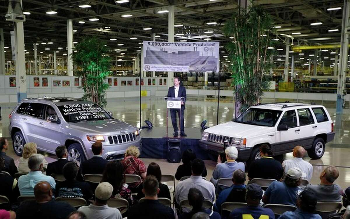 FILE - In this Tuesday, Aug. 13, 2013, file photo, Scott Garberding, senior vice president of manufacturing for Chrysler Group LLC stands between a 1992 Grand Cherokee, right, and the automaker's 5,000,000th vehicle produced at the Jefferson North Assembly Plant, in Detroit. Chrylser reports quarterly earnings on Wednesday, Oct. 30, 2013. (AP Photo/Carlos Osorio, File)