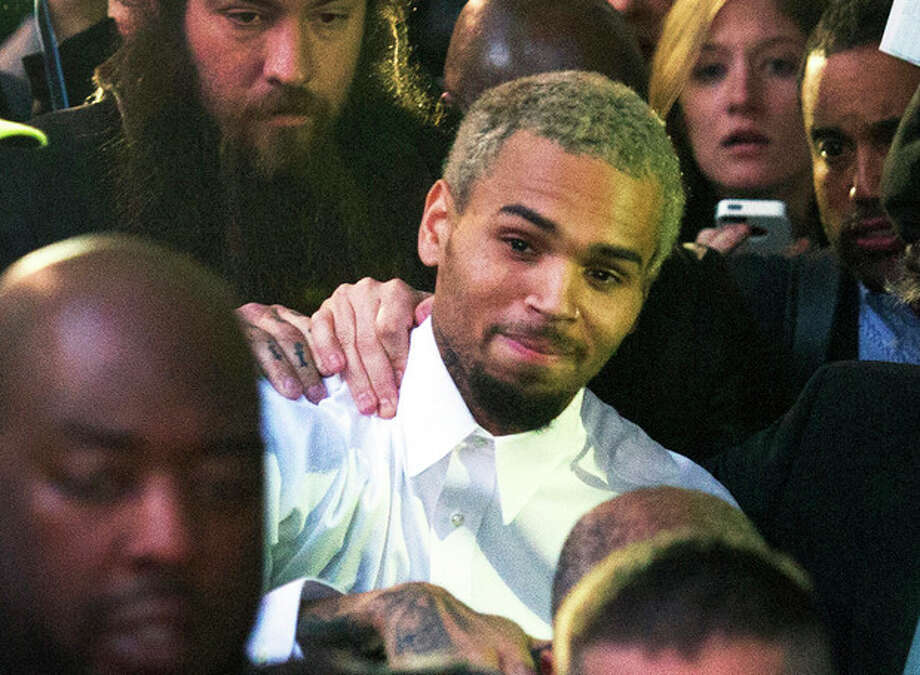 "FILE - In this Monday, Oct. 28, 2013 file photo, singer Chris Brown, center, departs the H. Carl Moultriel courthouse after he was released from jail following his arrest for allegedly punching another man, in Washington. A representative for the R&B star announced Tuesday, Oct. 29, 2013 that Brown has decided to go to rehab to ""gain focus and insight into his past and recent behavior, enabling him to continue the pursuit of his life and his career from a healthier vantage point."" (AP Photo/Cliff Owen, File) / FR170079 AP"