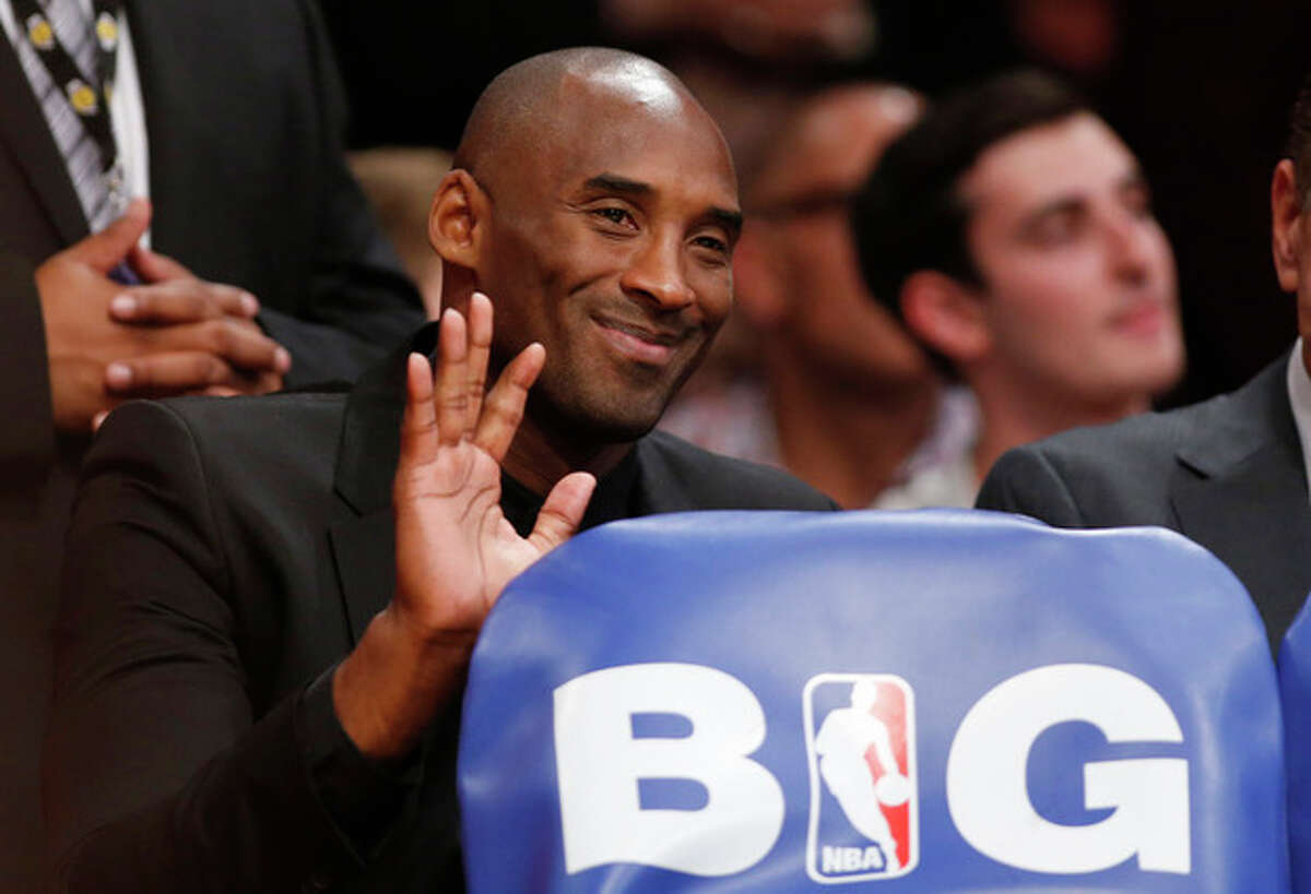 Los Angeles Lakers' Kobe Bryant waves as he sits behind the team's bench against the Los Angeles Clippers during the first half of an NBA basketball game in Los Angeles, Tuesday, Oct. 29, 2013. (AP Photo/Danny Moloshok)
