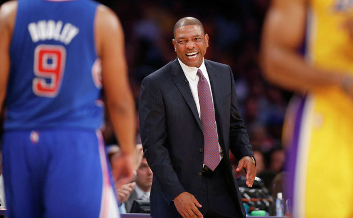 Los Angeles Clippers head coach Doc Rivers smiles during during the first half of an NBA basketball game in Los Angeles against the Los Angeles Lakers , Tuesday, Oct. 29, 2013. (AP Photo/Danny Moloshok)