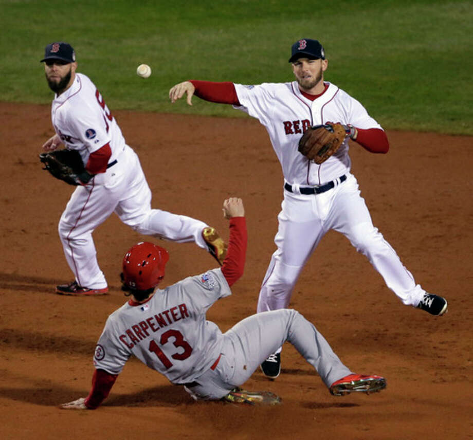Boston Red Sox's Stephen Drew throws over St. Louis Cardinals' Matt Carpenter (13) to turn a double play on a ball hit by David Ross during the third inning of Game 6 of baseball's World Series Wednesday, Oct. 30, 2013, in Boston. (AP Photo/Chris Carlson) / AP