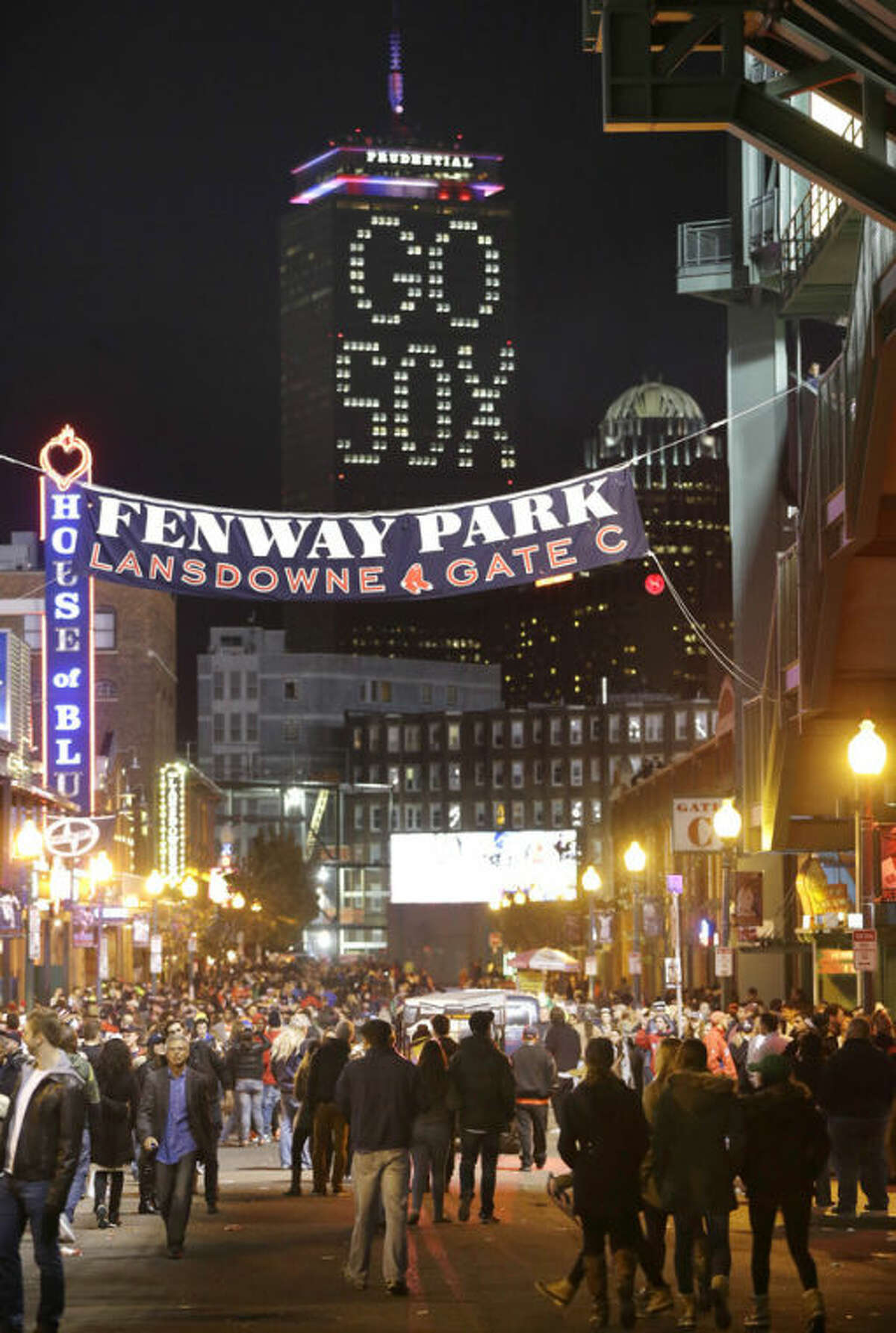 """The words """"Go Sox"""" are illuminated on a side of the Prudential Tower, top, as people walk along a street outside Fenway Park during Game 6 of baseball's World Series between the Boston Red Sox and St. Louis Cardinals, Wednesday, Oct. 30, 2013, in Boston. (AP Photo/Steven Senne)"""