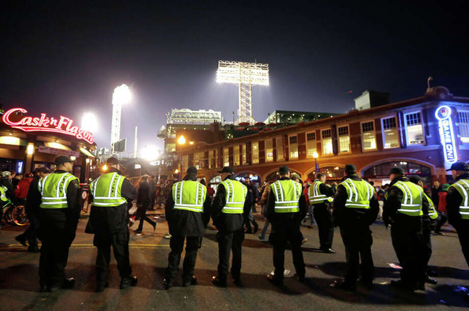 Law enforcement officials form a line along a street outside Fenway Park, background, following Game 6 of baseball's World Series between the Boston Red Sox and the St. Louis Cardinals, Wednesday, Oct. 30, 2013, in Boston. The Red Sox won 6-1 to win the series. (AP Photo/Steven Senne) / AP