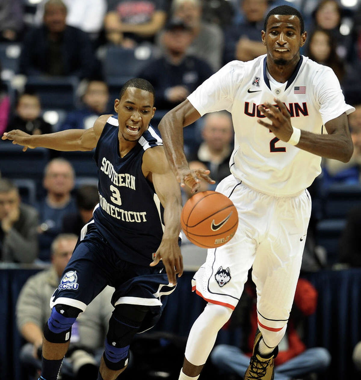 Connecticut's DeAndre Daniels, right, pushes ahead of Southern Connecticut's Michael Mallory, left, during the first half of an NCAA college basketball game, Wednesday, Oct. 30, 2013, in Storrs, Conn. (AP Photo/Jessica Hill)