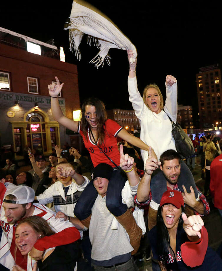 Boston Red Sox fans celebrate in the street near Fenway Park following Game 6 of baseball's World Series between the Red Sox and the St. Louis Cardinals on Wednesday, Oct. 30, 2013, in Boston. The Red Sox won 6-1 to win the series. (AP Photo/Steven Senne) / AP