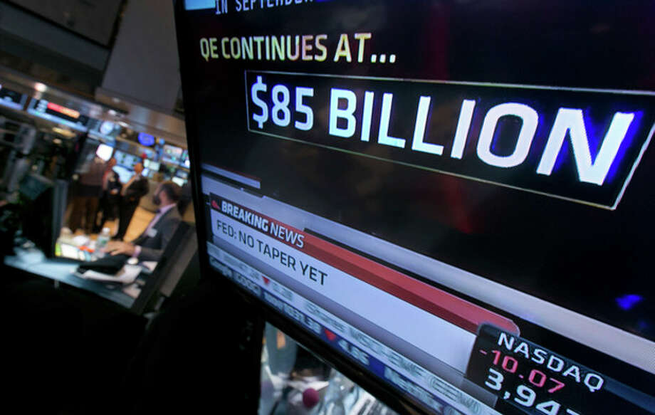 The decision of the Federal Reserve appears on a television screen on the floor of the New York Stock Exchange Wednesday, Oct. 30, 2013. The Fed says in a statement after a two-day policy meeting that it will keep buying $85 billion a month in bonds to keep long-term interest rates low and encourage more borrowing and spending. (AP Photo/Richard Drew) / AP