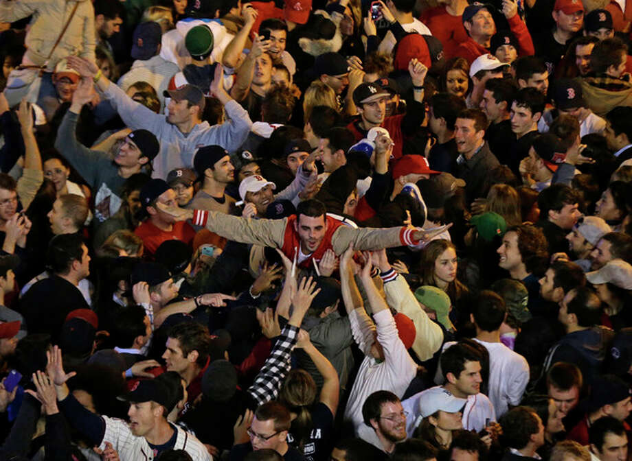Boston Red Sox fans celebrate after Boston defeated St. Louis Cardinals in Game 6 of baseball's World Series Wednesday, Oct. 30, 2013, in Boston. The Red Sox won 6-1 to win the series. (AP Photo/Charlie Riedel) / AP