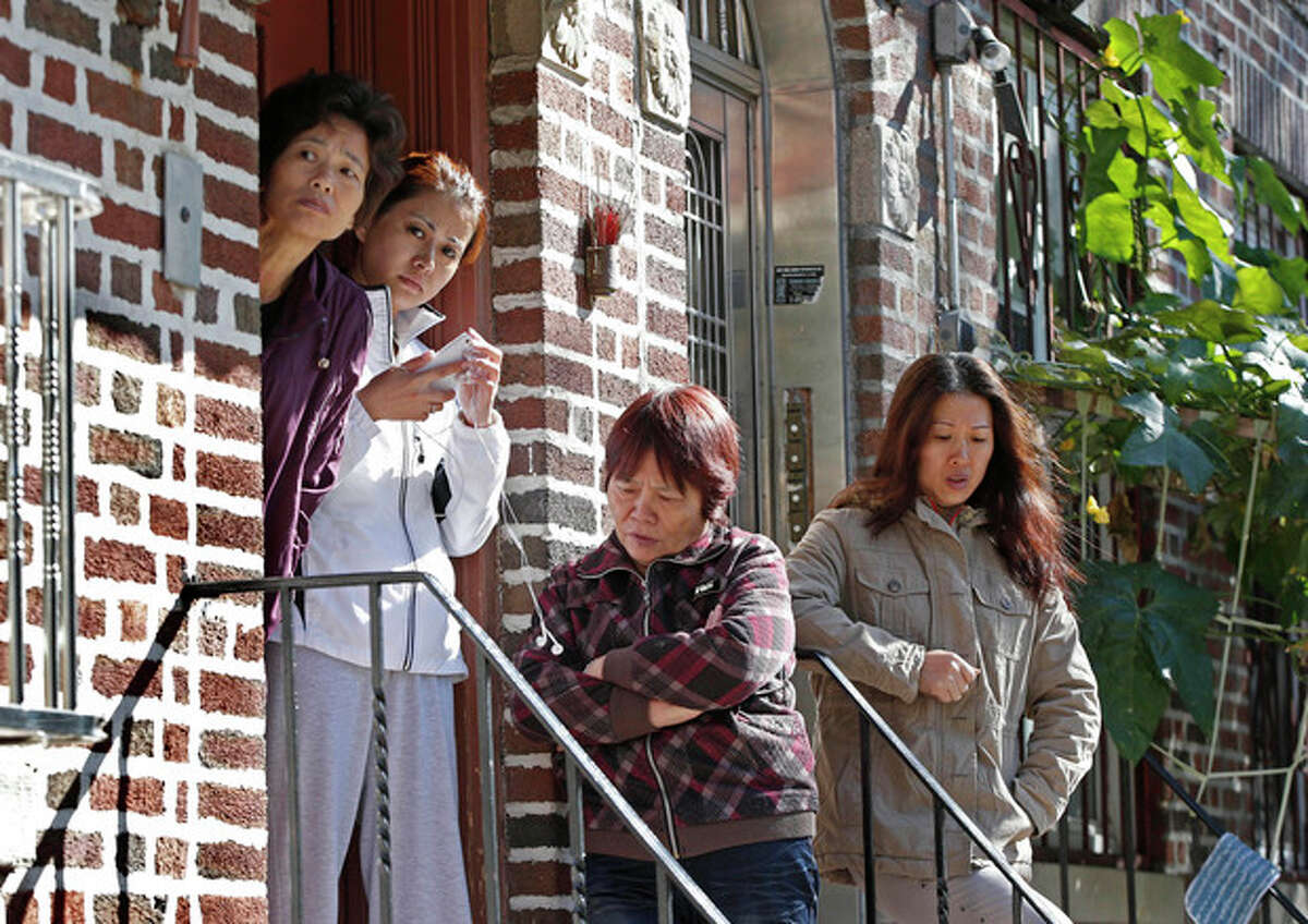 FILE - In this Sunday, Oct. 27, 2013 file photo, women gather on the steps of an apartment building opposite the scene of a fatal stabbing in New York. Police say a mother and her four young children were killed in a late night stabbing rampage at a Sunset Park, Brooklyn, home. A Chinese immigrant, 25-year-old Ming Don Chen, was arrested Sunday on five counts of murder in the deaths of his cousin's wife and her four children. (AP Photo/Kathy Willens)