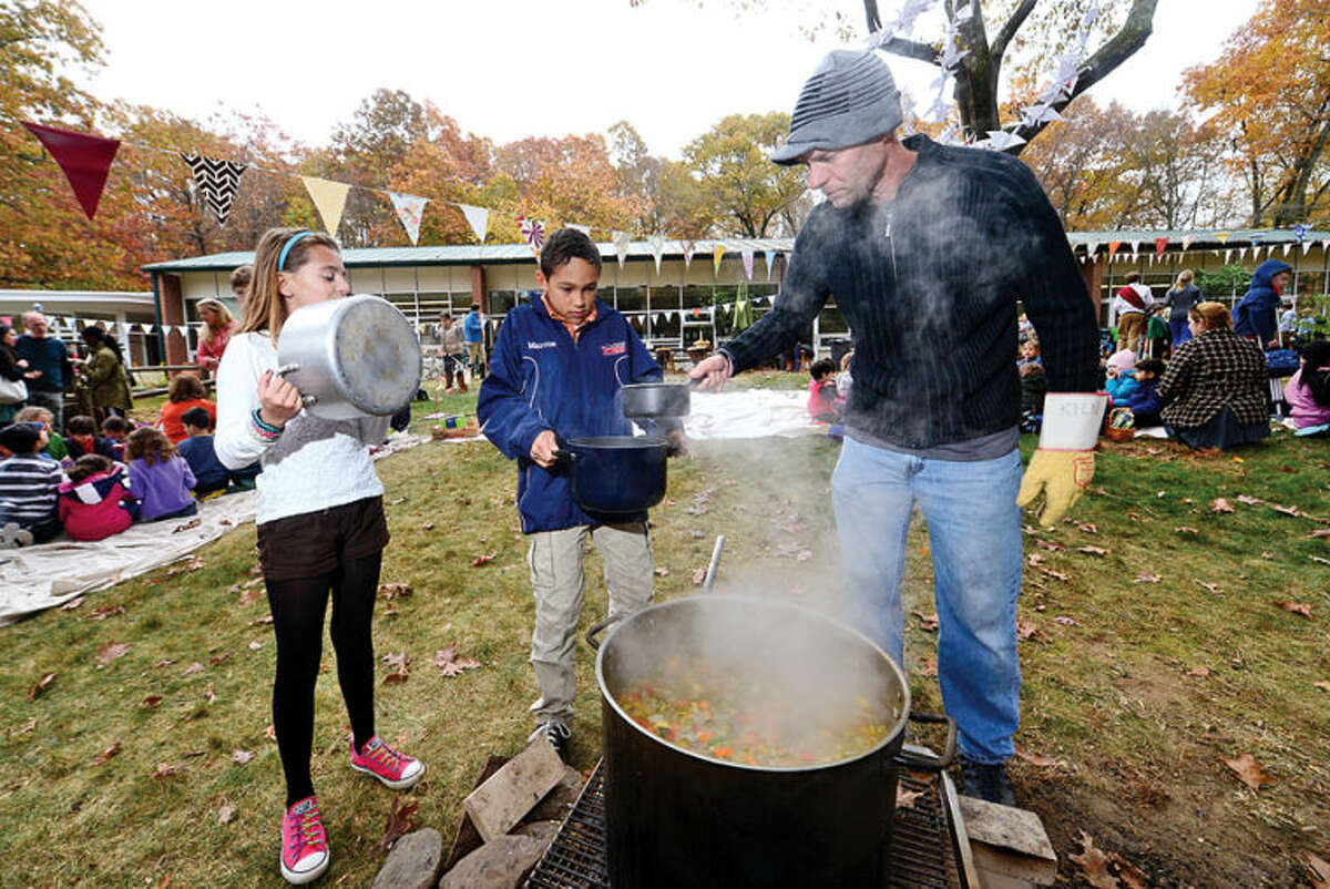Hour photo / Erik Trautmann The Montessori School 5th grader Marie Berliet and 6th grader Marcus Sang get homemade soup dished up by athletic director Jason Brasher during the Harvest festival as part of the school's 50th anniversary celebration in Wilton Thursday.