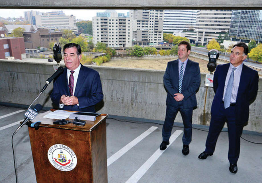 Hour photo / Erik Trautmann Mayor Michael A. Pavia holds a press conference to announce a resolution to a decades-long land-use issue at Parcel #38 aka The Hole in the Ground with Irone State Development's David Barry and FT Rich's Tom Rich Thursday at the Stamford Towne Center garage. / (C)2013, The Hour Newspapers, all rights reserved