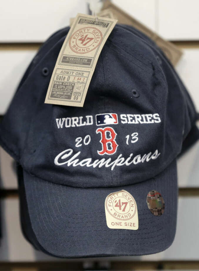 A Boston Red Sox 2013 baseball World Series champions cap hangs on a wall display at a shop outside Fenway Park, Thursday, Oct. 31, 2013 in Boston. The Red Sox defeated the St. Louis Cardinals 6-1 in Game 6 of baseball's World Series on Wednesday to win the series. (AP Photo/Steven Senne)
