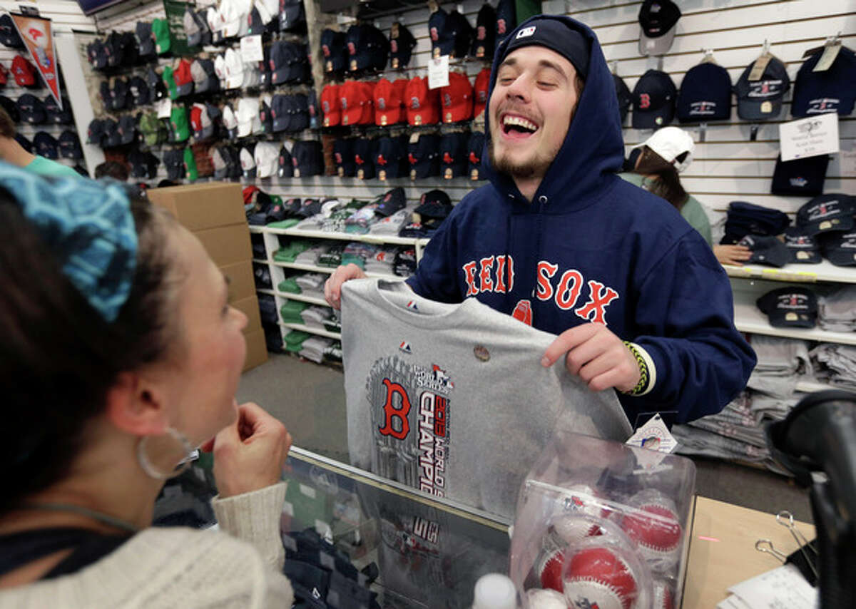 Worker Jake Miskin, of Boston, right, laughs with Lori Leduc, of Calgary, Alberta, Canada, left, as Leduc buys a 2013 baseball World Series champions shirt at a shop near Fenway Park in Boston, Thursday, Oct. 31, 2013. The Red Sox won Game 6 of baseball's World Series over the St. Louis Cardinals 6-1 Wednesday, Oct. 30, 2013, in Boston to win the series. (AP Photo/Steven Senne)