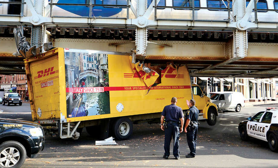 Hour photo / Erik Trautmann Police respond to Washington St and South Main St wherer a DHL delivery truck crashed under the Metro North train tressel.