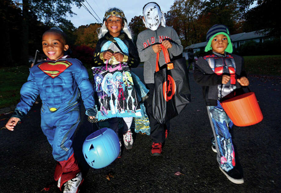 "Hour photo / Erik TrautmannJayden Bennett, 4, Zariyah Smith, 4, Jason Toigo, 8, and Alvin Love, 3, trick-or-treat in Norwalk Thursday evening. Trick-or-treating is ""on"" for the first time in two years. / (C)2013, The Hour Newspapers, all rights reserved"