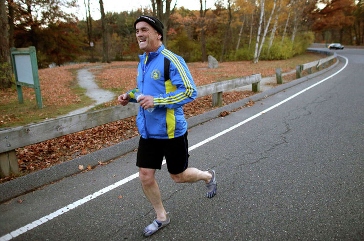 In this photo taken on Tuesday, Oct. 29, 2013, marathon runner Bill McCabe runs along a road in Stoneham, Mass. McCabe was stopped at mile 26 of the Boston Marathon after the April 15, 2013 bombings. He is running the New York Marathon to raise money for six people from his hometown. (AP Photo/Steven Senne)